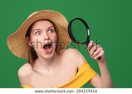 Shocked surprised woman wearing bright yellow dress and summer straw hat looking through the magnifying glass at the blank copy space, over green background - stock photo