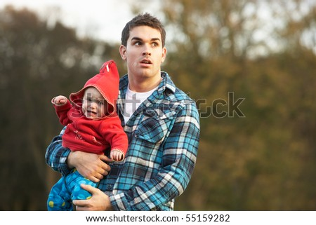 Shocked Teenage Boy Holding Baby - stock photo