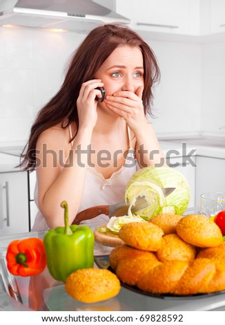 shocked unhappy young woman cooking in the kitchen and talking on the phone - stock photo