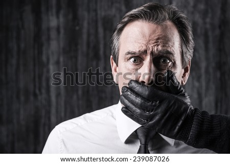 Shocked victim. Shocked businessman caught by a criminal holding hand on mouth of his victim - stock photo