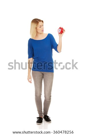 Shocked woman holding a clock. - stock photo
