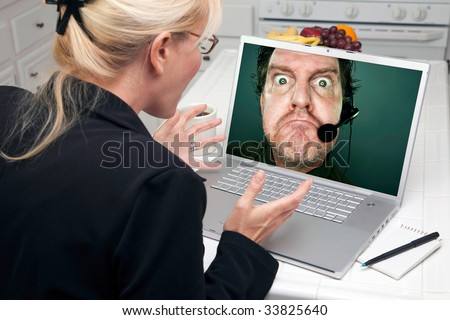 Shocked Woman In Kitchen Using Laptop with Grumpy Customer Support Man On Screen. Screen image can easily be replaced using the included clipping path. - stock photo