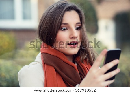 Shocked woman looking at mobile phone. Closeup portrait headshot beautiful young girl surprised student reading sms isolated cityscape outdoor background. Multicultural mixt race asian russian model - stock photo