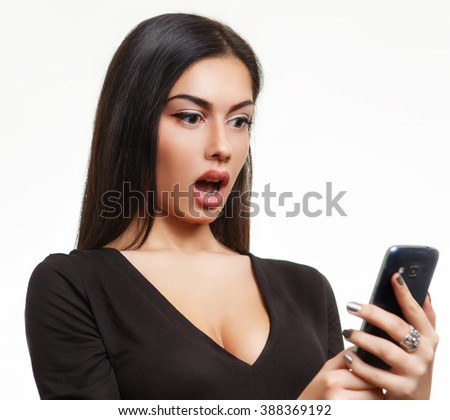 Shocked woman looking at phone - stock photo