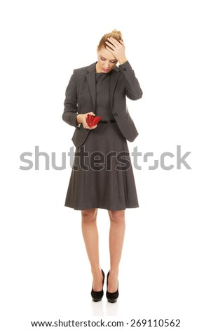 Shocked woman looking into her empty wallet. - stock photo