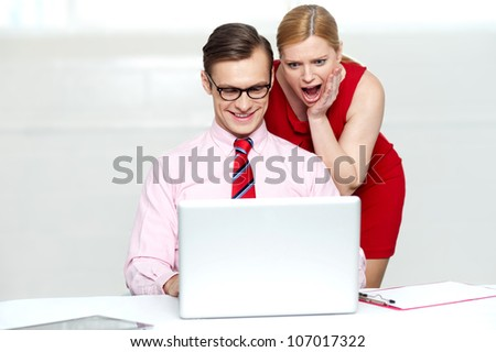 Shocked woman looking into laptop. Man working and smiling - stock photo