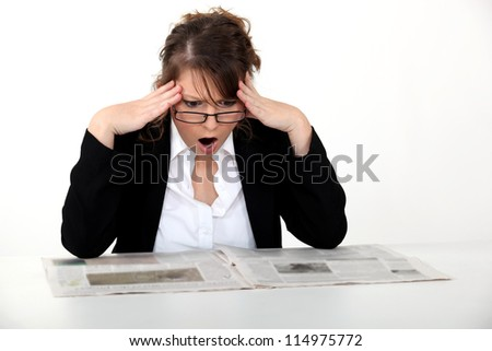 Shocked woman reading the newspaper