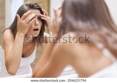 Shocked woman squeezing pimple in bathroom  - stock photo