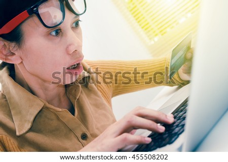 Shocked woman with laptop computer holding blank credit card, sitting at table, business background, business concept and selective focus.