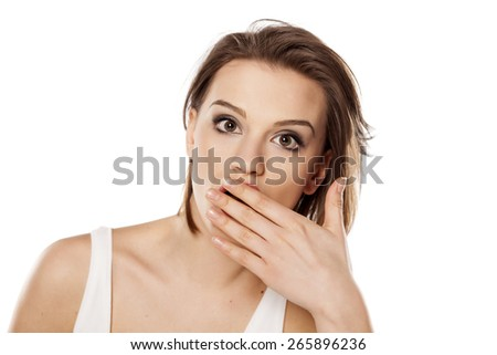 shocked young beautiful girl with hand over her mouth - stock photo