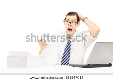 Shocked young businessman at his workplace looking at very expensive bill isolated on white background - stock photo