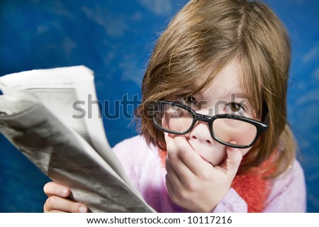 Shocked Young Girl Dressed Up in Reading Glasses Reading a Newspaper - stock photo