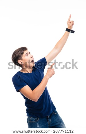 Shocked young man pointing finger up isolated on a white background - stock photo