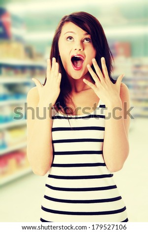 Shocked young woman in store - stock photo