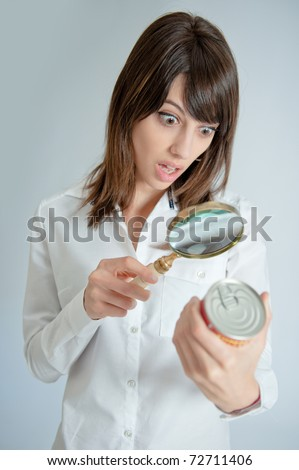 Shocked young   woman inspecting a can?s nutrition label with a magnifying glass - stock photo