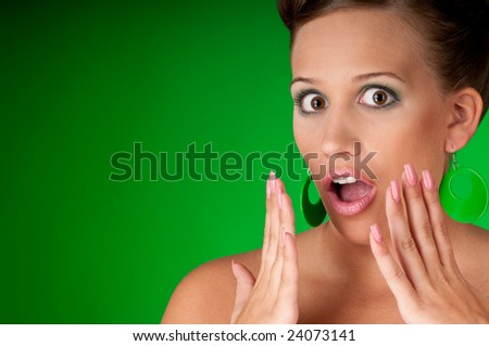 Shocked young woman on green background