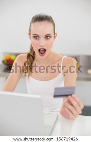 Shocked young woman using her laptop for online shopping in the kitchen at home - stock photo
