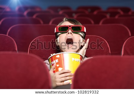 Shocked young woman with popcorn in 3D movie - stock photo