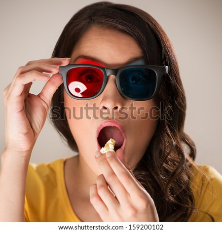 Shocked young woman with popcorn watching 3D movie - stock photo