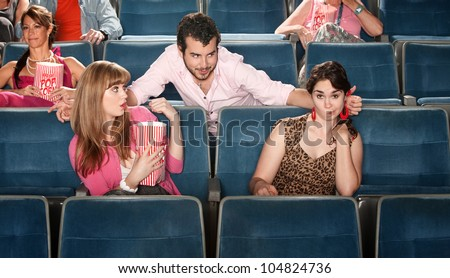 Shocked young women near flirting man in theater - stock photo