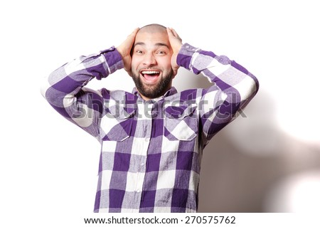 Shocking news! Surprised Young Arabic man touching his head while standing against white background. - stock photo