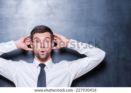 Shocking news. Surprised young man in shirt and tie expressing positivity and gesturing while standing against blackboard  - stock photo