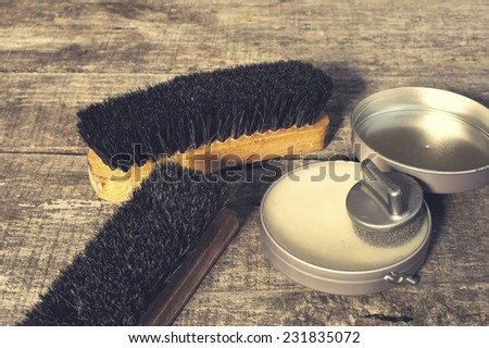 Shoe care. Shoe wax and brushes on wooden surface. Edited image with vintage effect - stock photo