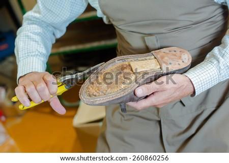 Shoe maker preparing a shoe - stock photo