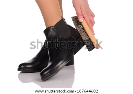 Shoe Polishing  with female legs in black boots isolated over white  - stock photo