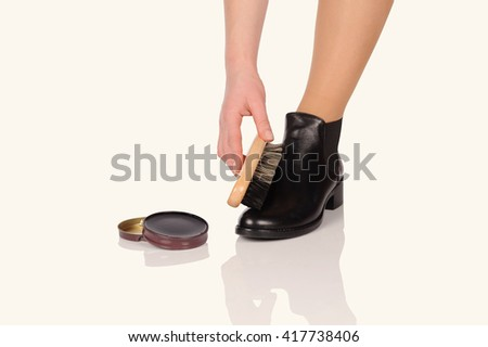 Shoe Polishing  with female legs in black boots isolated over white