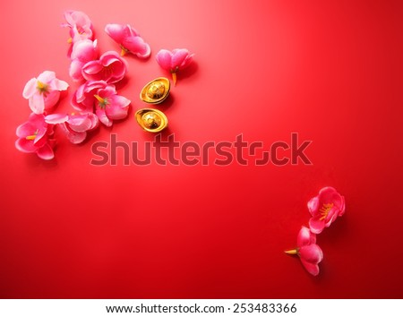 "Shoe-shaped gold ingot (Yuan Bao) (with the words ""zhao cai jin bao"" meaning money come in) and Plum Flowers on red background with copy space - best for Chinese New Year use - stock photo"
