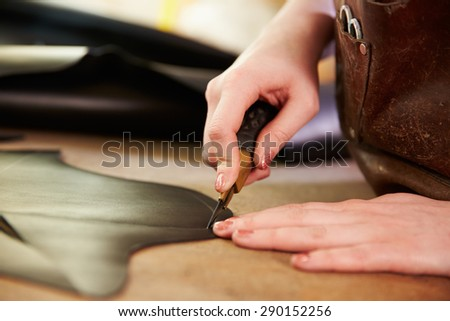 Shoemaker cutting leather in a workshop, close up - stock photo