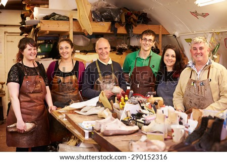 Shoemakers, group portrait in their workshop - stock photo