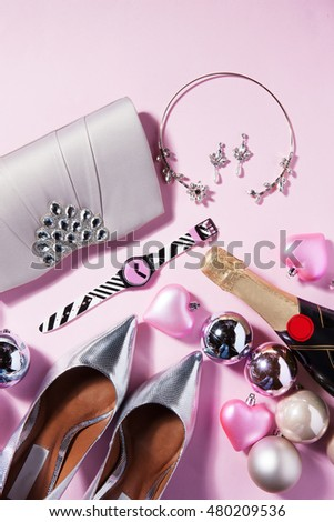 shoes bag and women accessories with a champagne and Christmas ornament and balls on a pink background