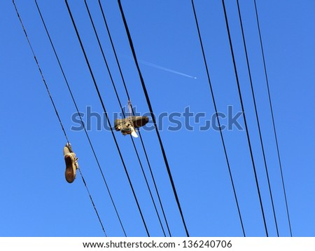 Shoes hanging from power lines contrasted with a jet airliner high overhead - stock photo