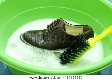 Shoes in a wash basin with soapy water - stock photo