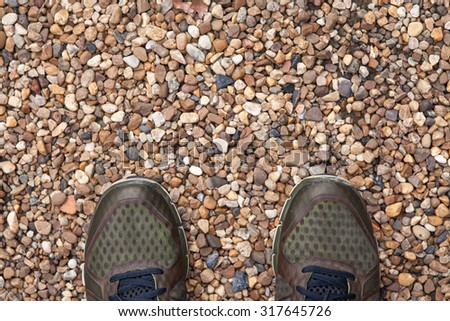 Shoes on small stones in concrete footpath texture - stock photo