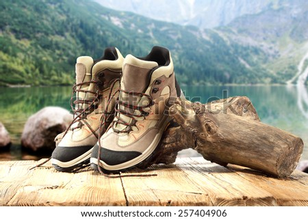 shoes on wooden old table and lake of green color  - stock photo