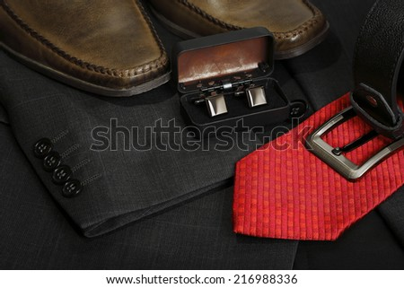 shoes, tie, belt and cufflinks on grey suit - stock photo