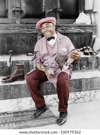 Shoeshine man working and smiling - stock photo