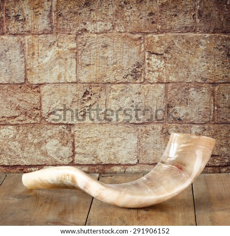 shofar (horn) on wooden table in front of jerusalem ancient wall. rosh hashanah (jewish holiday) concept . traditional holiday symbol. - stock photo