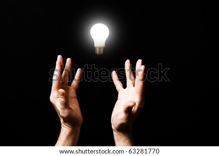 Shone electric lamp and hands of the person. - stock photo