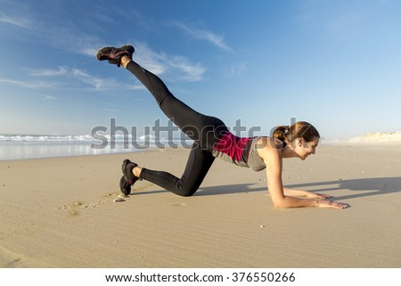 Shoot of a beautiful woman exercising herself in the beach - stock photo