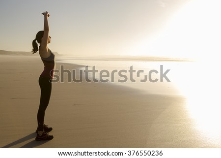 Shoot of a beautiful woman making stretching exercises in the beach - stock photo