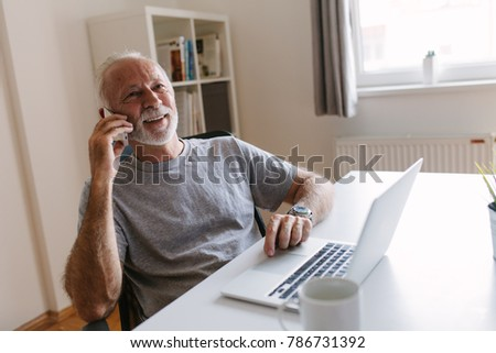 shoot of elderly man working in his home office.