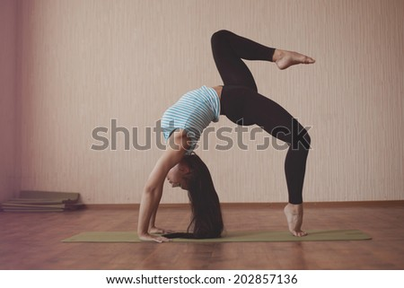 Shoot of young caucasian gymnast with long hair when she warming up