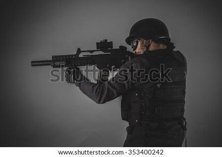 shooting, airsoft player with gun, helmet and bulletproof vest on gray background - stock photo