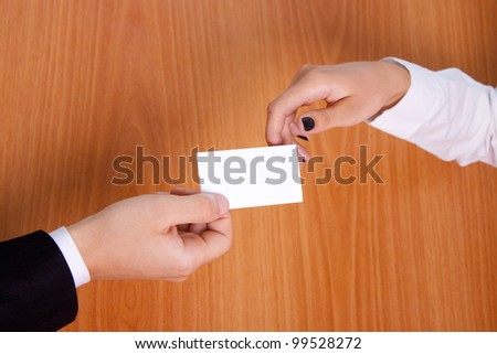 Shooting hand the business card. Women's and man's hand. background table. - stock photo