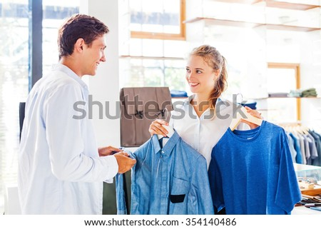 shop assistant helping to choose clothes in a store - stock photo
