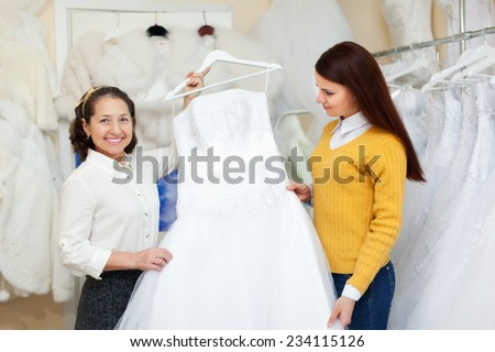 Shop assistant  helps the bride in choosing bridal gown at shop of wedding fashion - stock photo